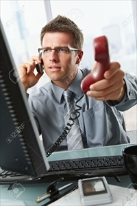 6338862-Businessman-with-glasses-busy-talking-on-mobile-phone-handing-over-landline-call-to-answer-in-office-Stock-Photo_R.jpg